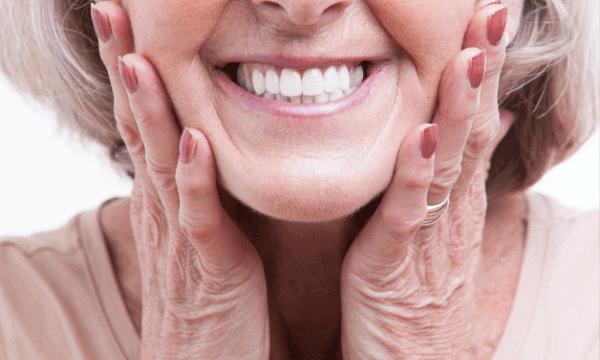 Kobieta nosząca protezę - jakie są rodzaje protez zębowych?